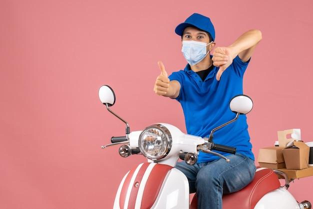 Widok z góry na dostawcę kciuki w górę i w dół w masce medycznej w kapeluszu siedzącym na skuterze na pastelowym tle brzoskwini