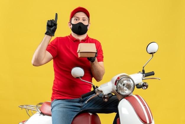 Widok z góry na dostawcę ubrany w czerwoną bluzkę i rękawiczki w masce medycznej siedzi na skuterze, pokazując zamówienie skierowane w górę