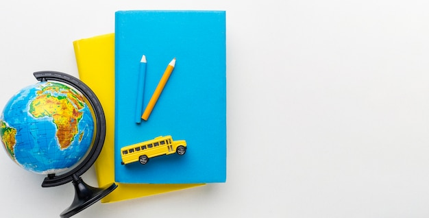 Widok z góry na drewnianą kulę ziemską z książkami i autobusem szkolnym
