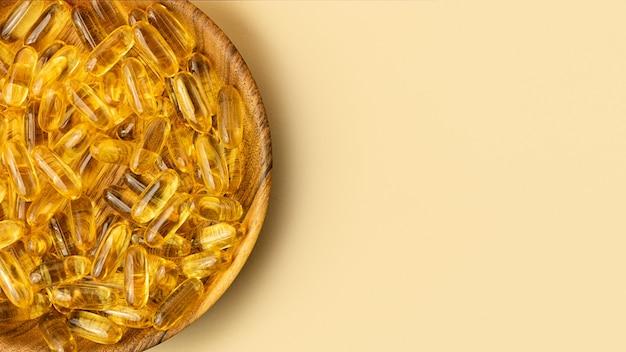 Widok z góry na drewnianą płytkę z żółtymi kapsułkami oleju rybnegoskopiuj miejsce na textlarge baner