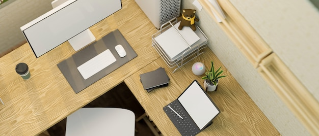 Widok z góry na drewniane biurko komputerowe lshape z makietą pustego ekranu komputera i tabletu