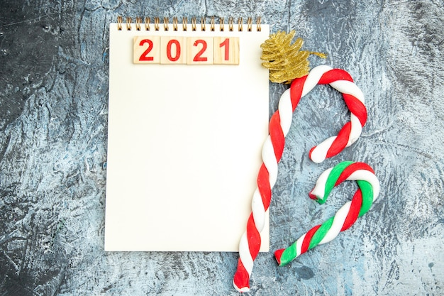 Widok z góry na drewniane klocki na notebookach świątecznych cukierków na szarym tle