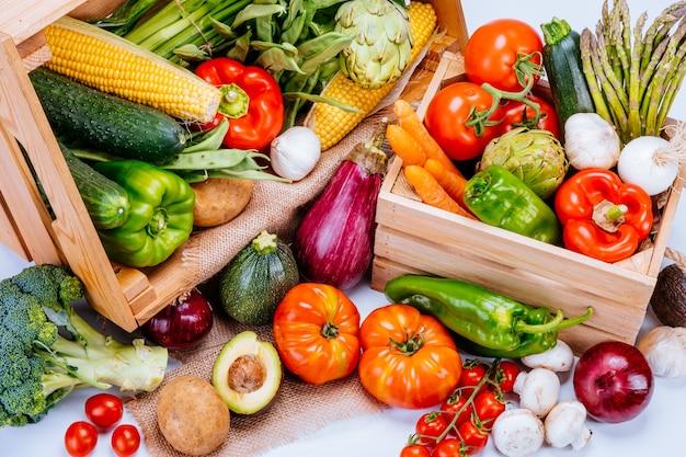 Widok z góry na drewniane pudełka pełne świeżych warzyw na białym tle, idealne do zbilansowanej diety