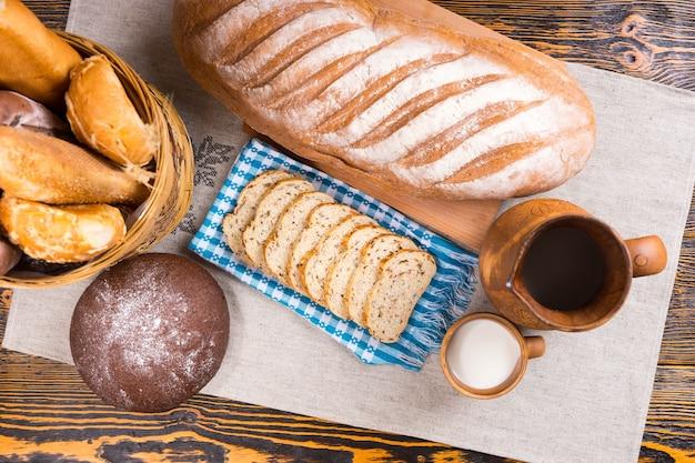 Widok z góry na drewniany dzban, mały kubek mleka i różne bochenki chleba i kromki obok kosza na stole