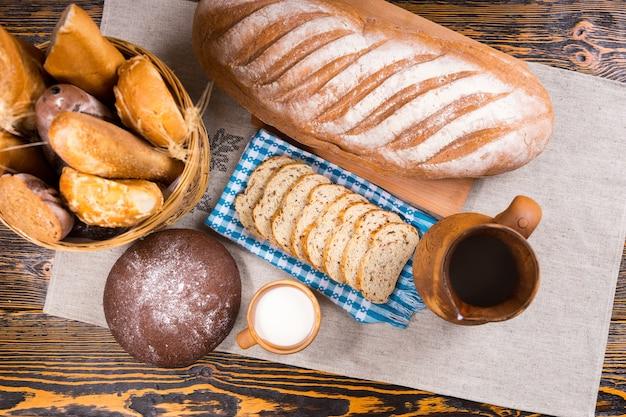 Widok z góry na drewniany dzbanek, małą filiżankę mleka i świeżo upieczony chleb jako cały bochenek i kromki obok kosza na stole
