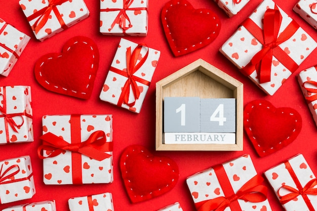Widok z góry na drewniany kalendarz, białe pudełka na prezenty i czerwone tekstylne serca
