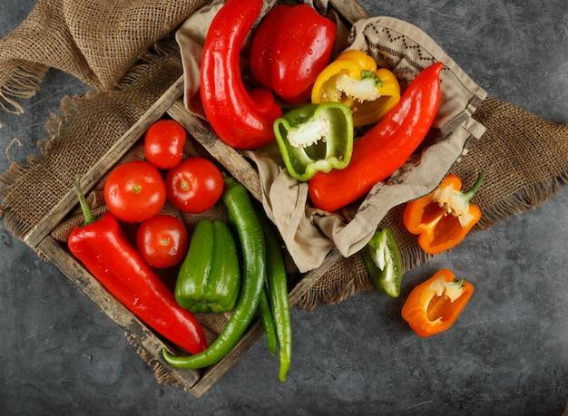 Widok z góry na drewniany pojemnik papryki i pomidorów.