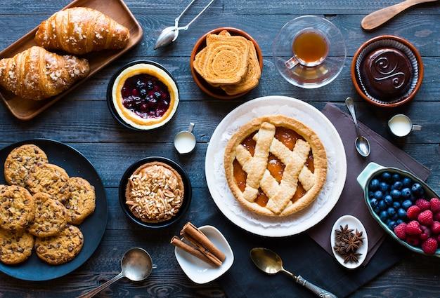 Widok z góry na drewniany stół pełen ciast, owoców, kawy, herbatników, przypraw i innych