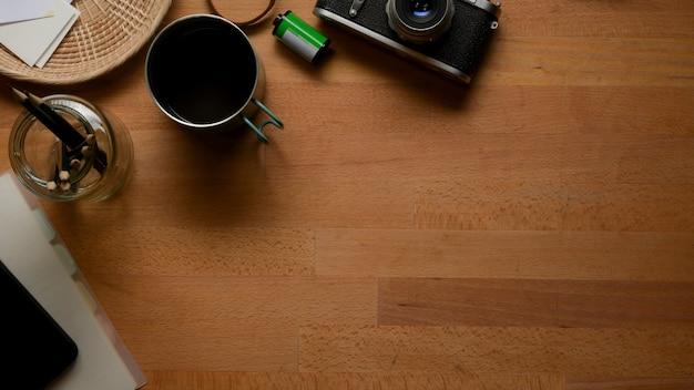 Widok z góry na drewniany stół roboczy z miejscem na kopię, kubkiem do kawy, aparatem i materiałami eksploatacyjnymi w pokoju biurowym