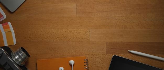Widok z góry na drewniany stół z aparatem, notatnikiem, zapasami i miejscem na kopię