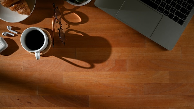 Widok z góry na drewniany stół z miejscem na kopię, laptop, filiżankę kawy i materiały eksploatacyjne w pokoju biurowym
