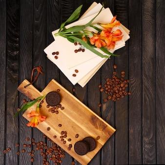 Widok z góry na drewniany stół z porozrzucanymi ziarnami kawy, ciasteczkami, kwiatami i książkami