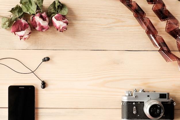 Widok z góry na drewniany stół ze smartfonem, słuchawkami, aparatem vintage, filmem i suszonymi różami z liśćmi