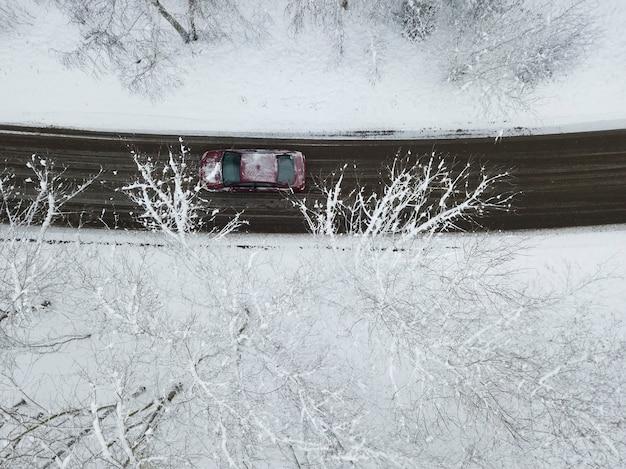 Widok z góry na drogę przez pokryty śniegiem las, po którym jedzie samochód