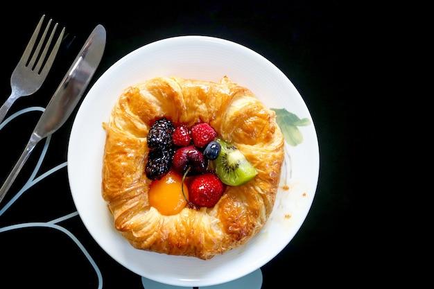 Widok z góry na duńskie ciasto z remiksem owoców na białym talerzu.