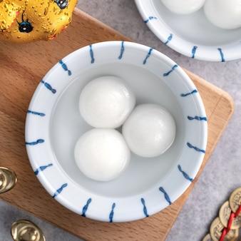 Widok z góry na duże tangyuan yuanxiao (kulki z kleistego ryżu) na chińskie jedzenie na festiwal księżycowego nowego roku, słowa na złotej monecie oznaczają nazwę dynastii, którą stworzyła.