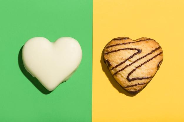 Widok z góry na dwa czekoladowe ciasteczka w kształcie serca na zielonym i różowym tle