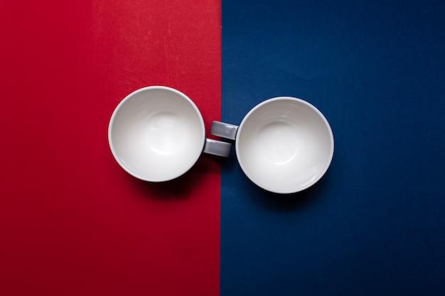 Widok z góry na dwa kubki ceramiczne na tle kolorów czerwonego i niebieskiego.