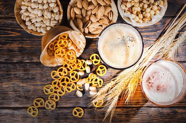Widok z góry na dwie szklanki ze świeżo nalanym ciemnym i jasnym piwem w pobliżu pszenicy, porozrzucane małe precle i pistacje na ciemnym drewnianym biurku. koncepcja żywności i napojów