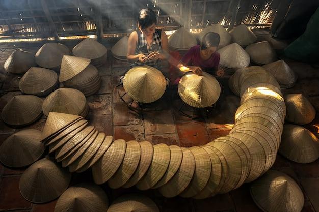 Widok z góry na dwie wietnamskie siostry rzemieślnika wykonującego tradycyjny wietnamski kapelusz