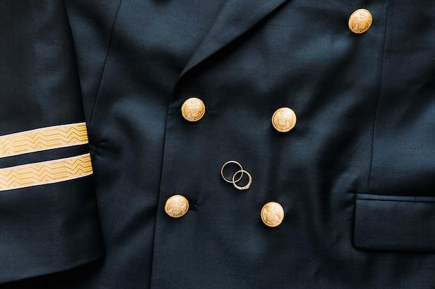 Widok z góry na dwie złote obrączki na czarnej męskiej marynarce z guzikami z dwugłowym orłem