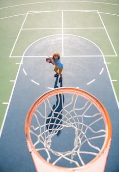 Widok z góry na dziecko grające w koszykówkę trzymające piłkę ze szczęśliwą twarzą