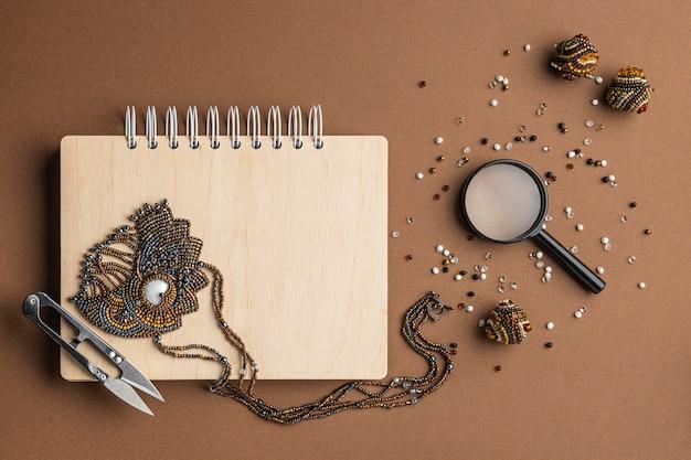 Widok z góry na elementy niezbędne do pracy z koralikami z notatnikiem i lupą