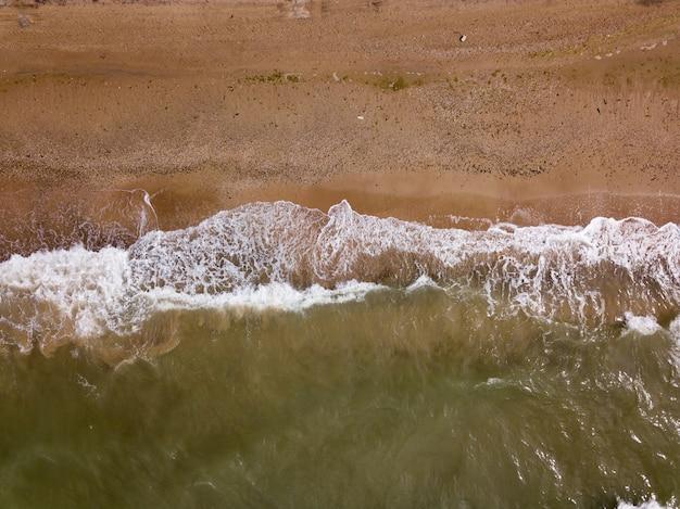 Widok z góry na fale rozbijające się o piasek, przelatujące nad tropikalną piaszczystą plażą i falami