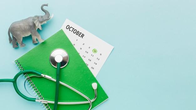 Widok z góry na figurkę słonia ze stetoskopem i kalendarzem na dzień zwierząt
