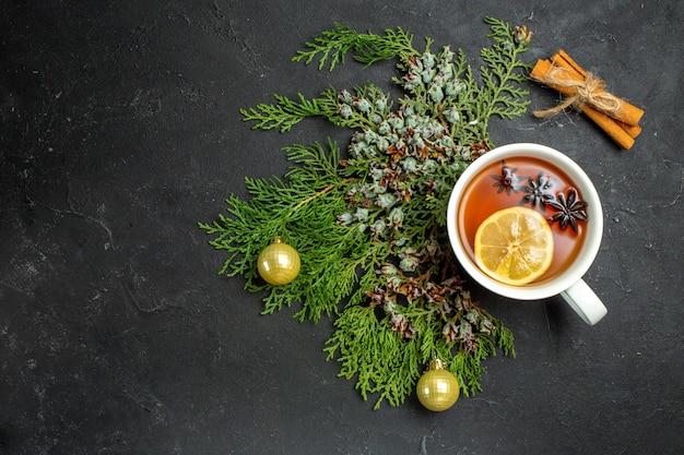 Widok z góry na filiżankę akcesoriów świątecznych czarnej herbaty i limonki cynamonowe na czarnym tle