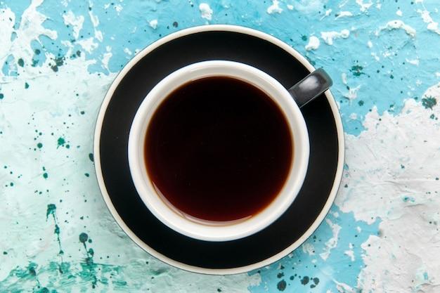 Widok z góry na filiżankę gorącego napoju herbaty wewnątrz płyty na jasnoniebieskiej powierzchni