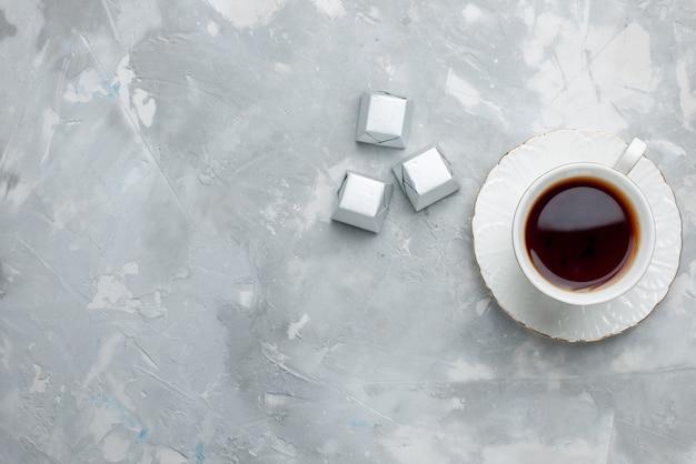 Widok z góry na filiżankę gorącej herbaty w białej filiżance na szklanym talerzu ze srebrnym opakowaniem czekoladowe cukierki na lekkim biurku, napój herbaciany słodkie czekoladowe ciasteczko