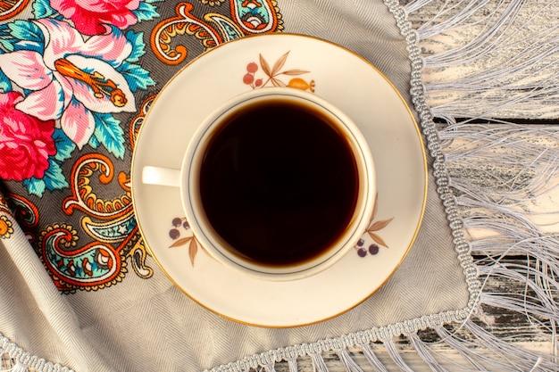 Widok z góry na filiżankę gorącej i mocnej kawy na szarym drewnianym biurku