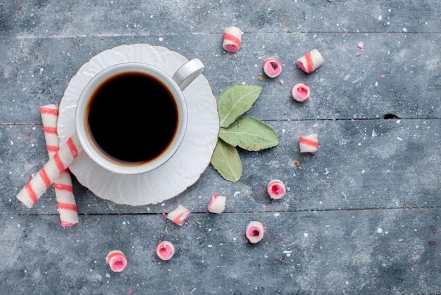 Widok z góry na filiżankę gorącej i mocnej kawy wraz z różowymi cukierkami w sztyfcie na szarym, słodkim napoju kawowym