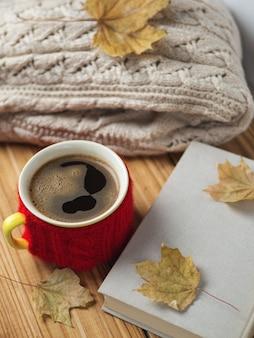 Widok z góry na filiżankę gorącej kawy, ciepły sweter i starą książkę