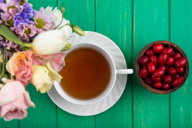 Widok z góry na filiżankę herbaty na spodek i miskę jagód dereń z kwiatami na zielonym tle