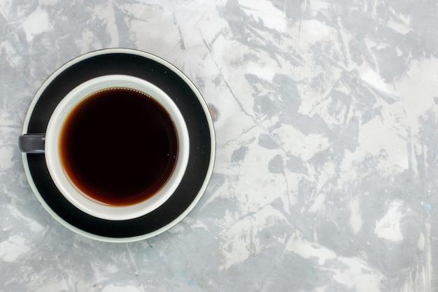 Widok z góry na filiżankę herbaty w filiżance i talerz na jasnobiałej powierzchni