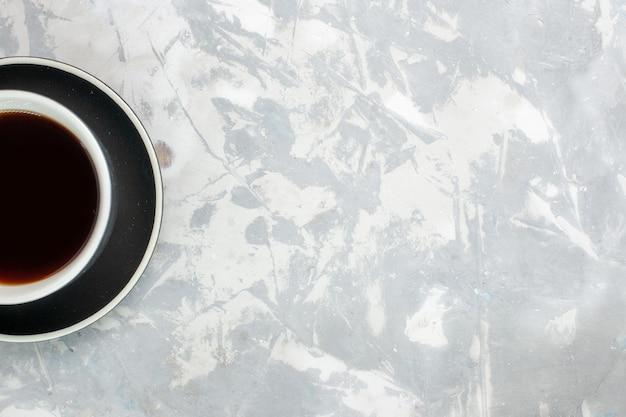 Widok z góry na filiżankę herbaty w filiżance i talerz na jasnobiałym biurku