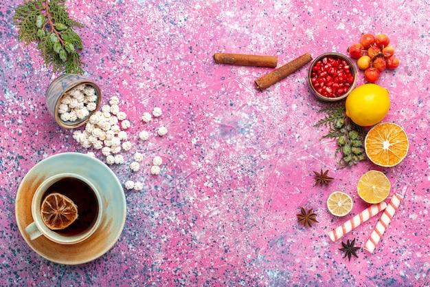Widok z góry na filiżankę herbaty z białymi słodkimi konfiturami i cynamonem na jasnoróżowym biurku