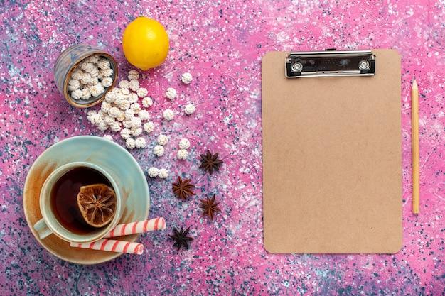 Widok z góry na filiżankę herbaty z białymi słodkimi konfiturami i cytryną na różowym biurku