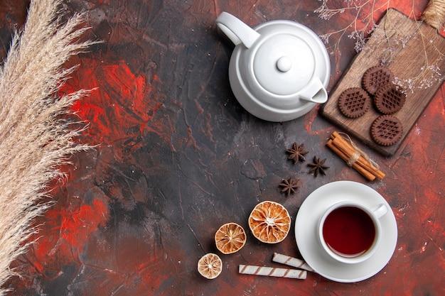 Widok z góry na filiżankę herbaty z ciasteczkami czekoladowymi na ciemnym herbatniku na biurku
