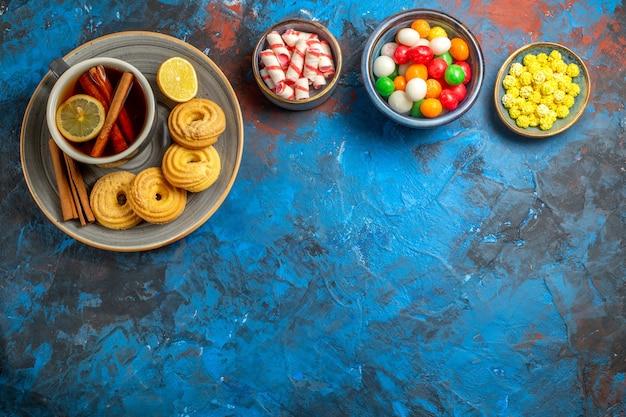 Widok z góry na filiżankę herbaty z ciasteczkami i cukierkami na jasnoniebieskiej herbacie z cukierków stołowych
