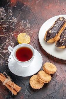 Widok z góry na filiżankę herbaty z ciasteczkami i eklerami na ciemnym stole cukrowym herbatniki herbaciane słodkie