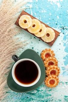 Widok z góry na filiżankę herbaty z ciasteczkami i suszonymi krążkami ananasa na jasnoniebieskiej powierzchni