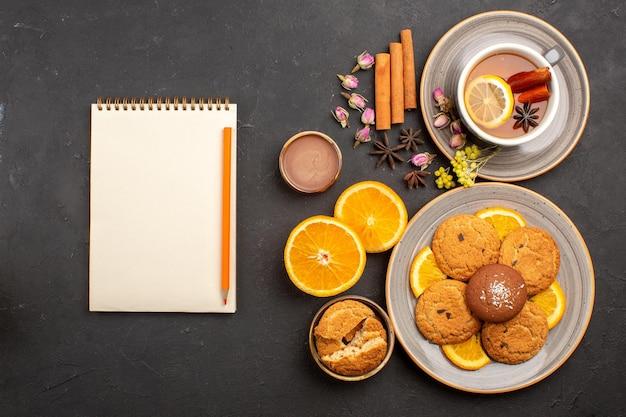 Widok z góry na filiżankę herbaty z ciasteczkami i świeżymi pokrojonymi pomarańczami na ciemnej powierzchni ciasteczka z herbatnikami ze słodkiej herbaty
