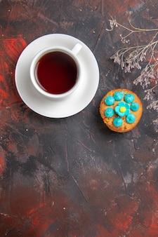 Widok z góry na filiżankę herbaty z ciasteczkami na ciemnym stole