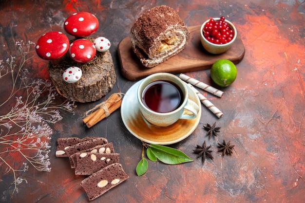 Widok z góry na filiżankę herbaty z ciastem i herbatnikami na ciemnej powierzchni