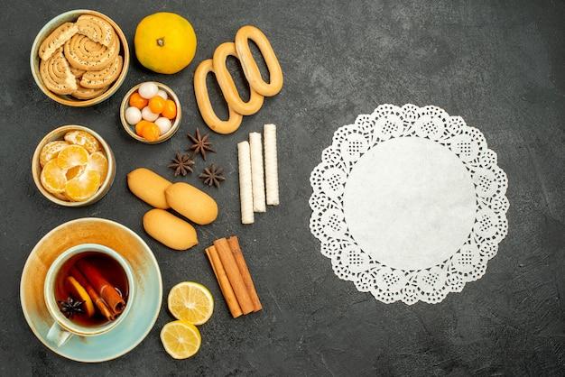 Widok z góry na filiżankę herbaty z cukierkami, herbatnikami i owocami na szarym stole herbata słodkie ciasteczko