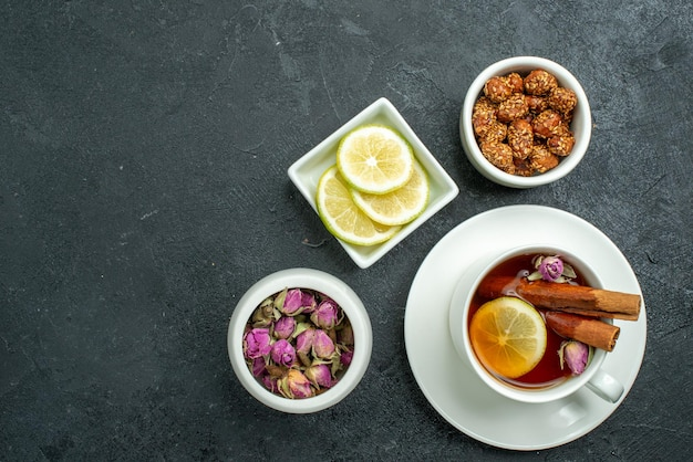Widok z góry na filiżankę herbaty z cukierkami i herbatą na ciemnej powierzchni ceremonii owocowej cytrusowej herbaty