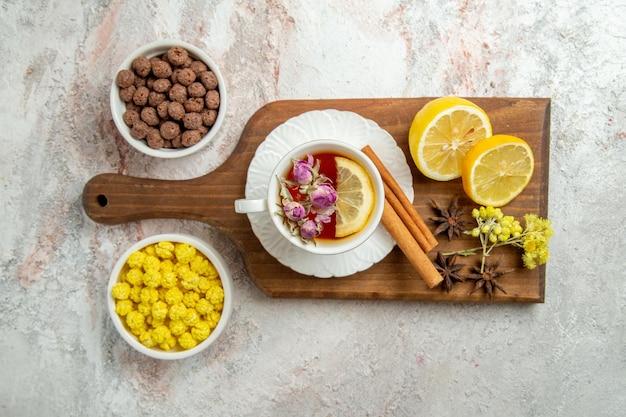 Widok z góry na filiżankę herbaty z cukierkami i plasterkami cytryny na białej przestrzeni